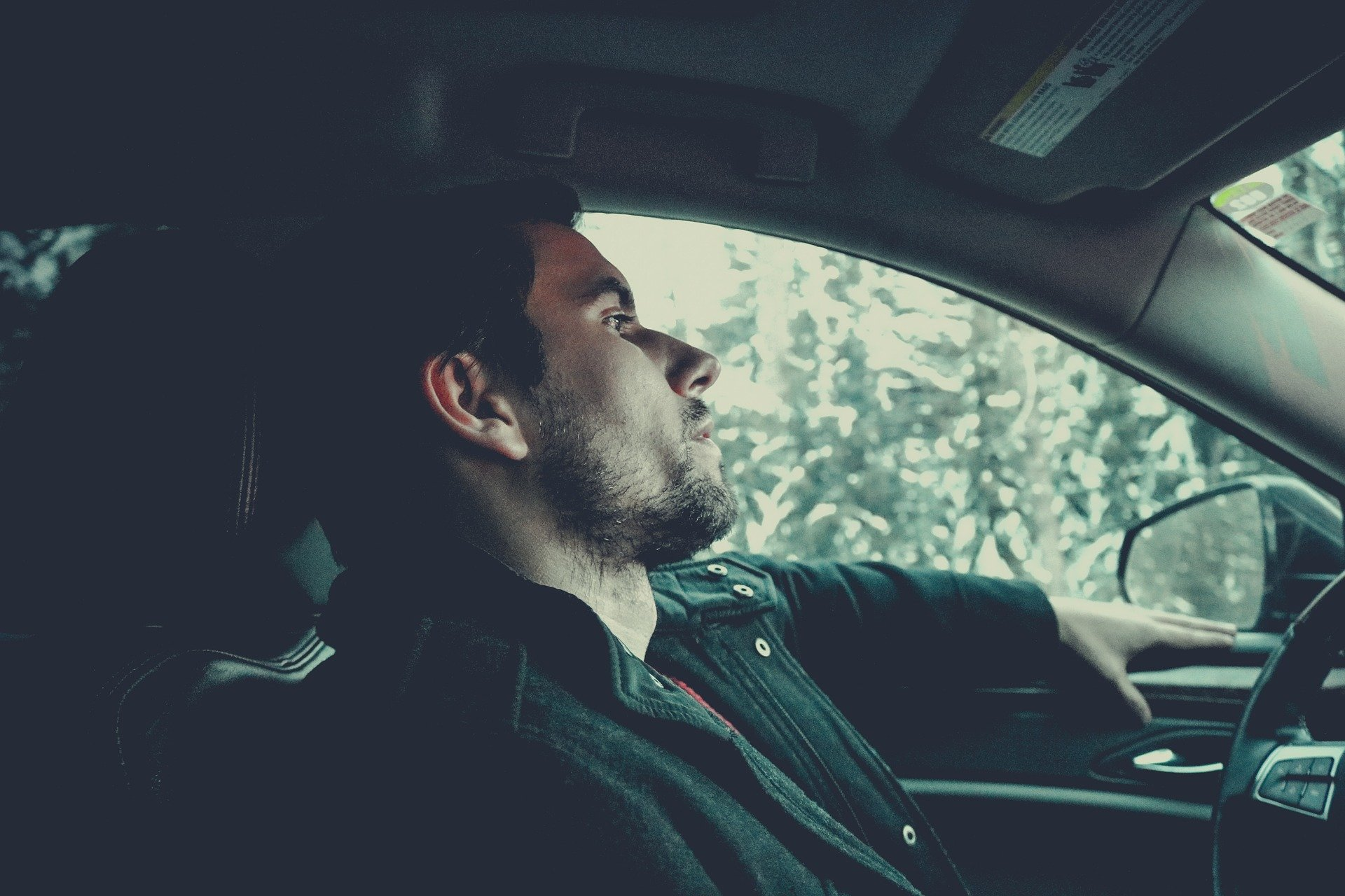 Pictured - A young man in deep thoughts while inside a car   Source: Pixabay