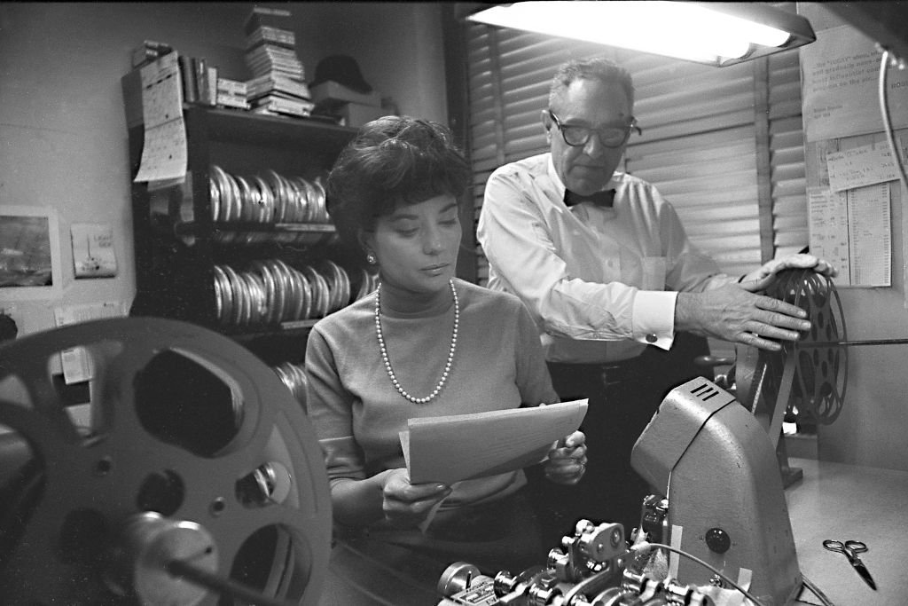 American broadcast journalist Barbara Walters reviews a script as an unidentified man threads a projector at NBC Studios, New York, New York, 1966.   Source: Getty Images