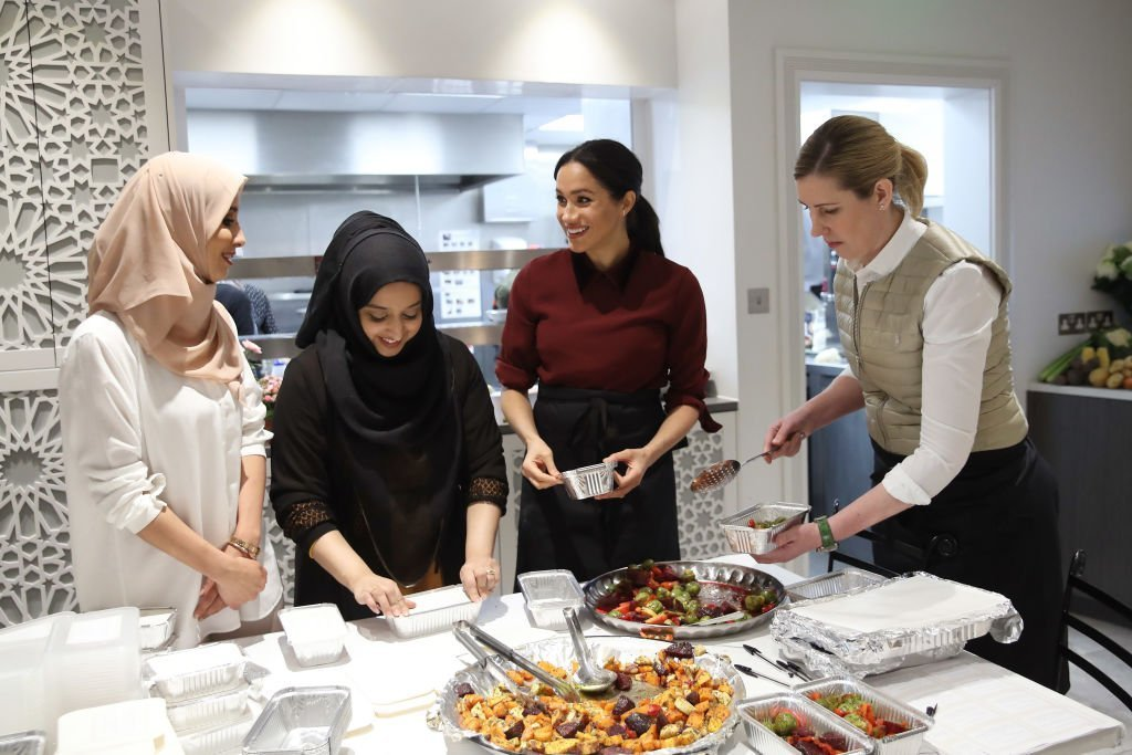 Meghan, Duchess of Sussex with chef Clare Smyth (R) and kitchen co-ordinator Zaheera Sufyaan (2L) as she visits the Hubb Community Kitchen. | Photo: Getty Images