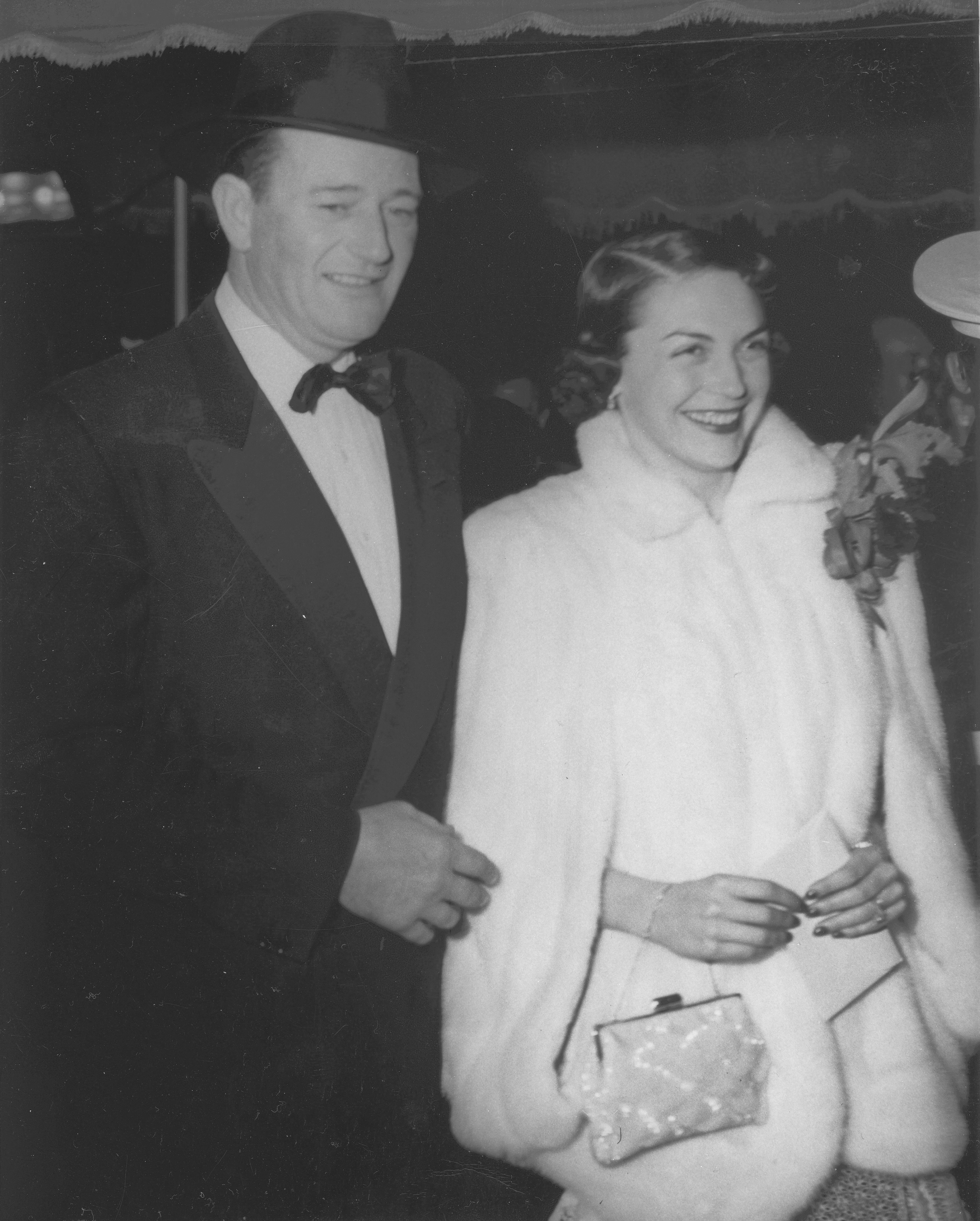 """John Wayne and his wife, Esperanza Baur arrive at the """"Sands of Iwo Jima"""" premiere.   Source: Wikimedia Commons By USMC Archives, CC BY 2.0"""