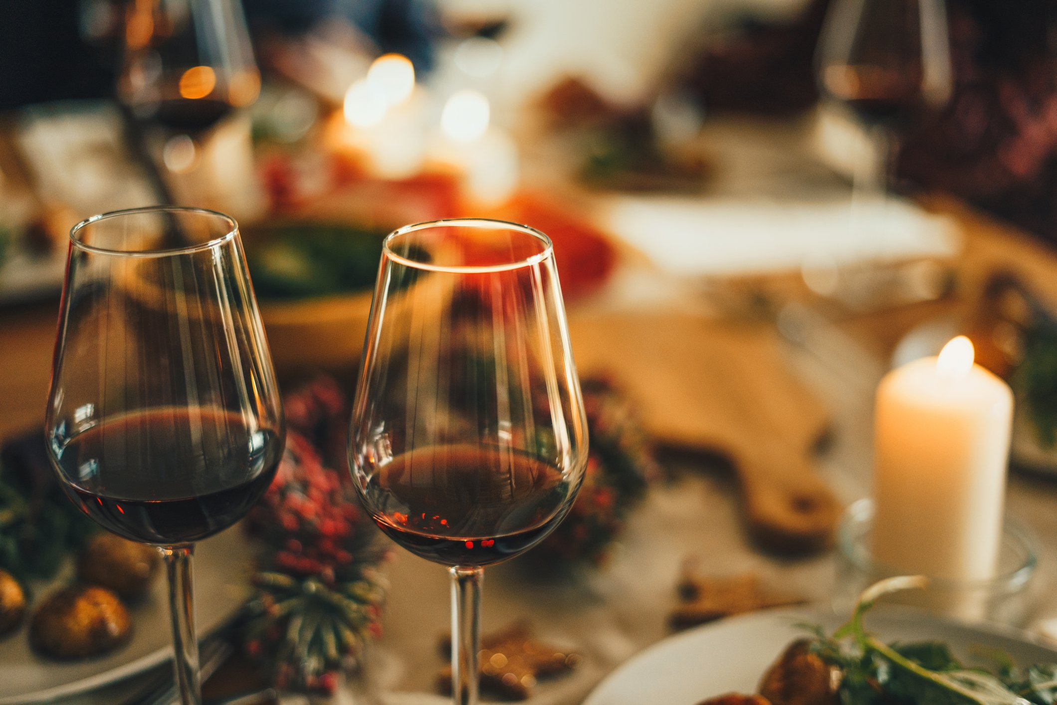 A close up shot of red wine glasses at Christmas dinner table. | Photo: Getty Images
