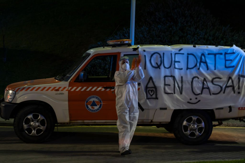 A young woman from Civil Protection applauds at 8 pm in front of her car with the banner Stay at home to encourage them during the mandatory quarantine decreed by the government as a result of the coronavirus (Covid-19) in Santander, Spain, on March 28, 2020. I Foto: Getty Images