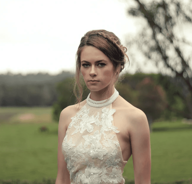 An upset bride stares directly ahead of her and has a look of disdain on her face   Unsplash/Christopher Campbell