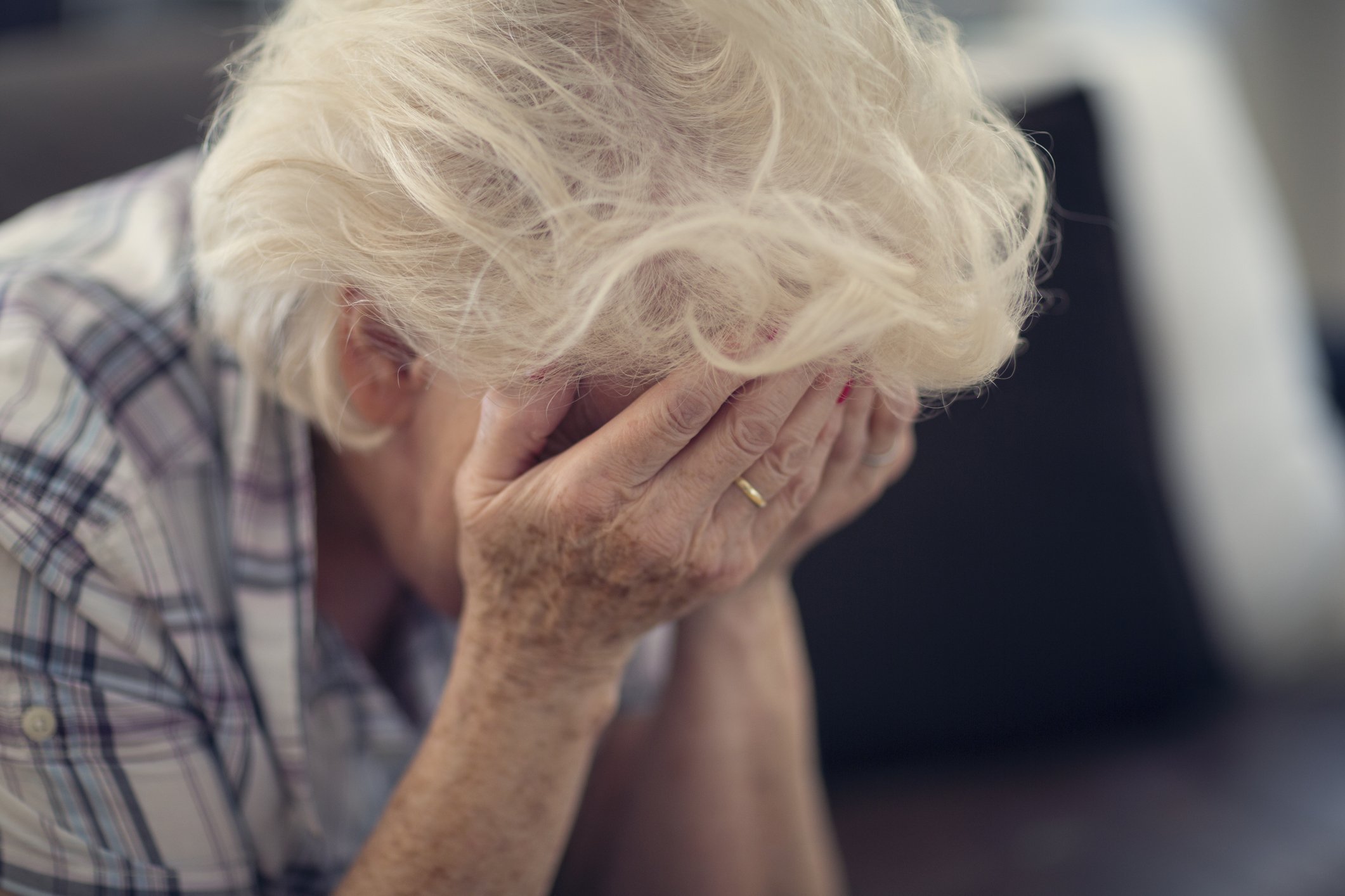 Senior woman buries her face in her hands in despair   Photo: Getty Images