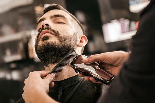 A barber trimming a client's beard / Photo: Getty Images