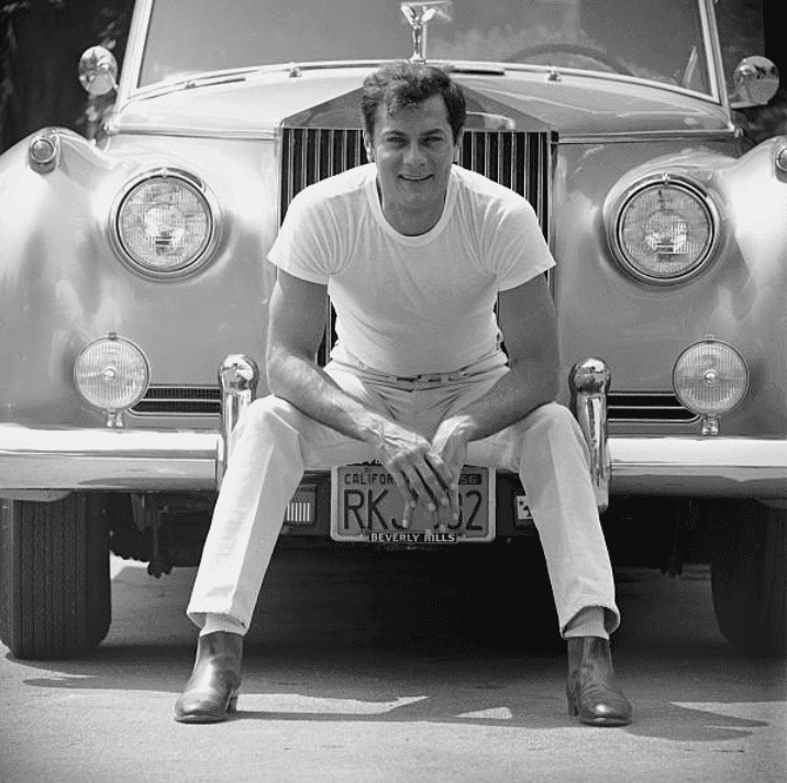 Tony Curtis sitting in front of his Rolls Royce, in 1961, Los Angeles, California | Source: Getty Images (Photo by Ralph Crane/The LIFE Picture Collection)