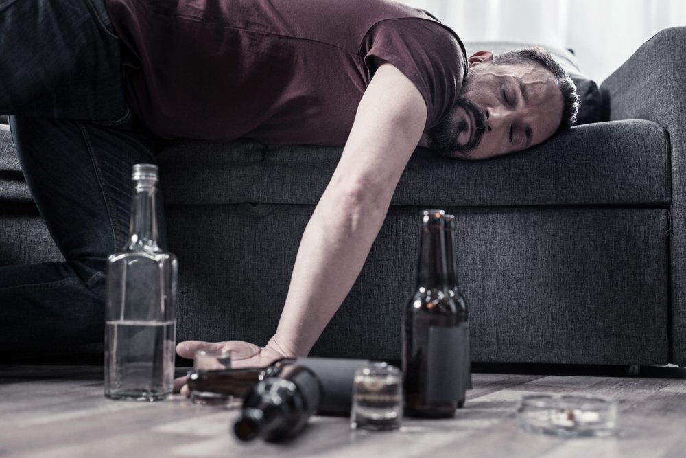 A drunk bearded adult man lying on the sofa and sleeping. | Photo: Shutterstock