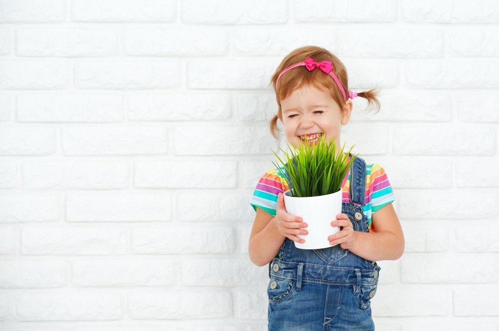 Happy girl holding a potted plant. | Photo: Shutterstock