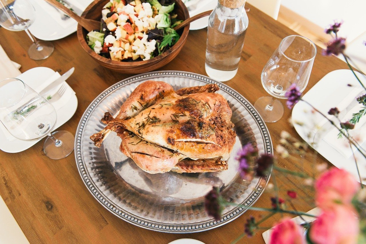 A decked out dining table with a roasted chicken in the center | Photo: Pixabay/Free-Photos