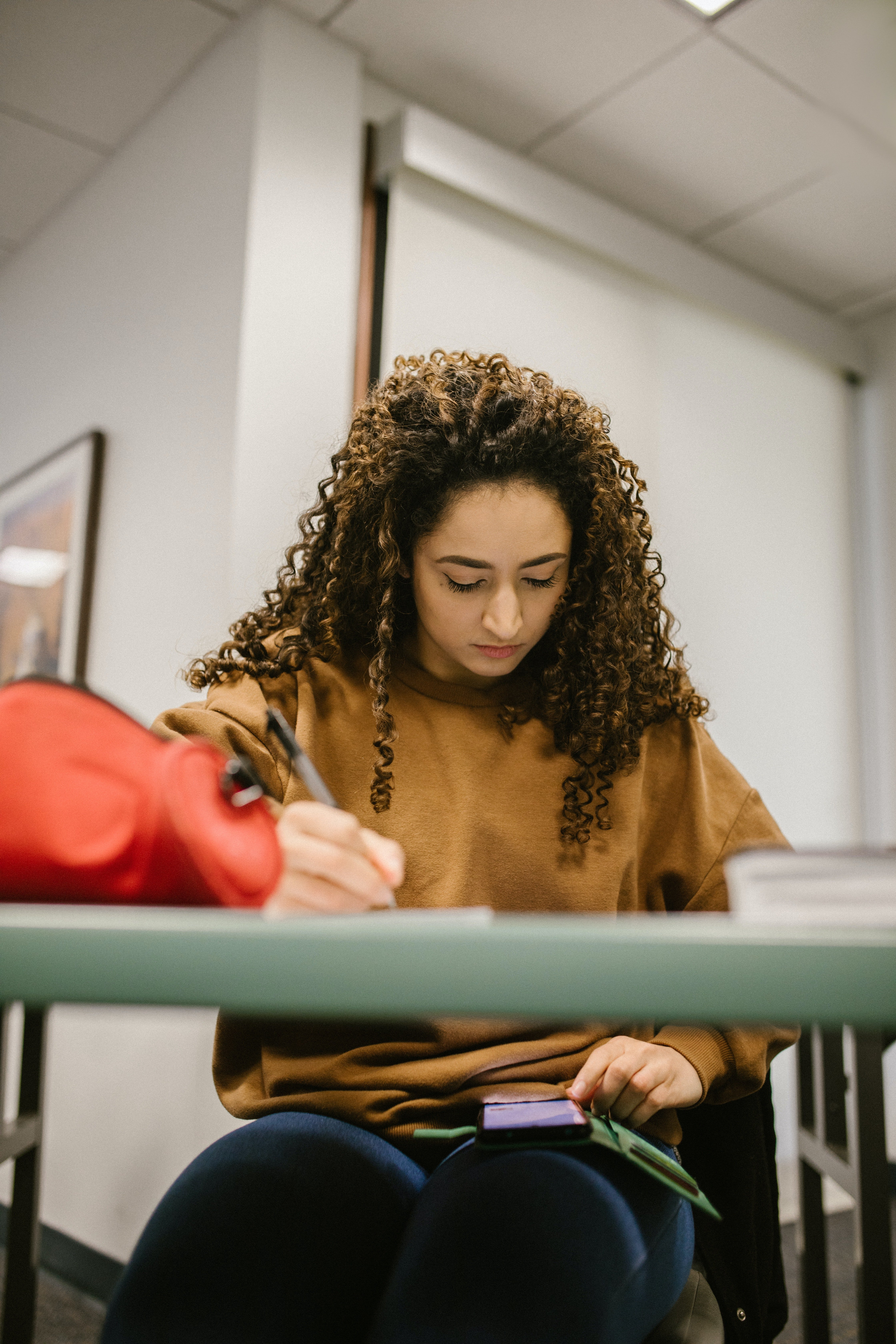 A female student writing a test with a phone on her lap.   Pexels/ RODNAE Productions