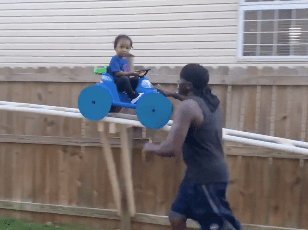A screenshot of the devoted grandfather running alongside his grandson while riding the roller coaster he built. | Source: Twitter/HUNNITBANDBRIA
