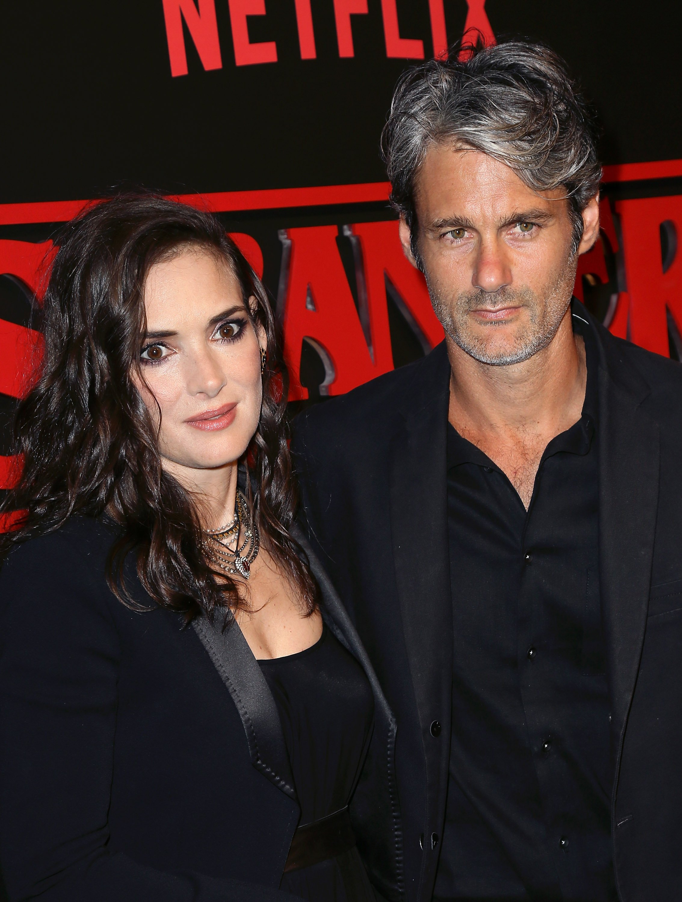 "Winona Ryder and Scott Mackinlay Hahn attend the premiere of Netflix's ""Stranger Things"" on July 11, 2016, in Los Angeles, California. 