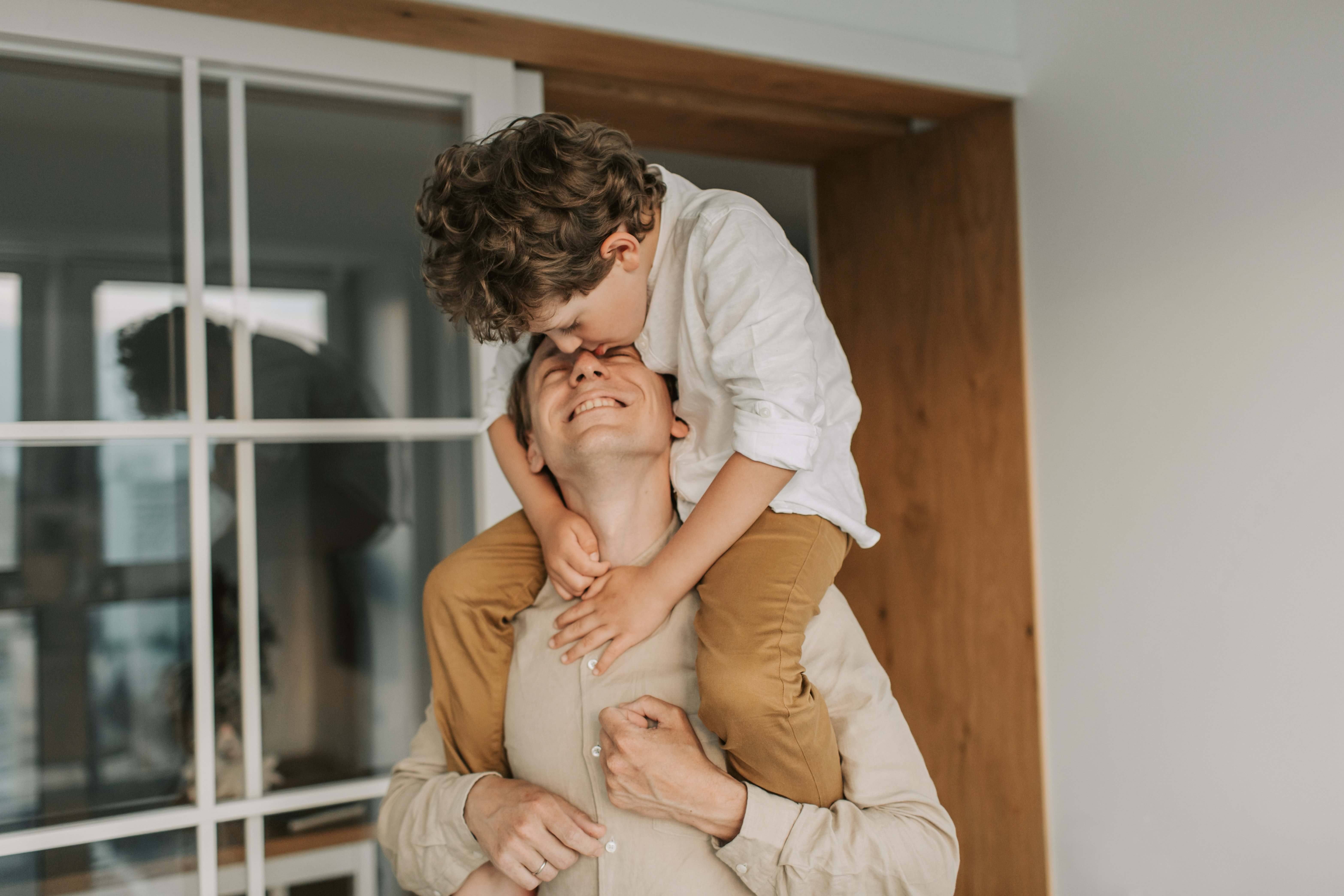 Pictured - A man carrying his son on his shoulders wearing coordinated outfits | Source: Pexels