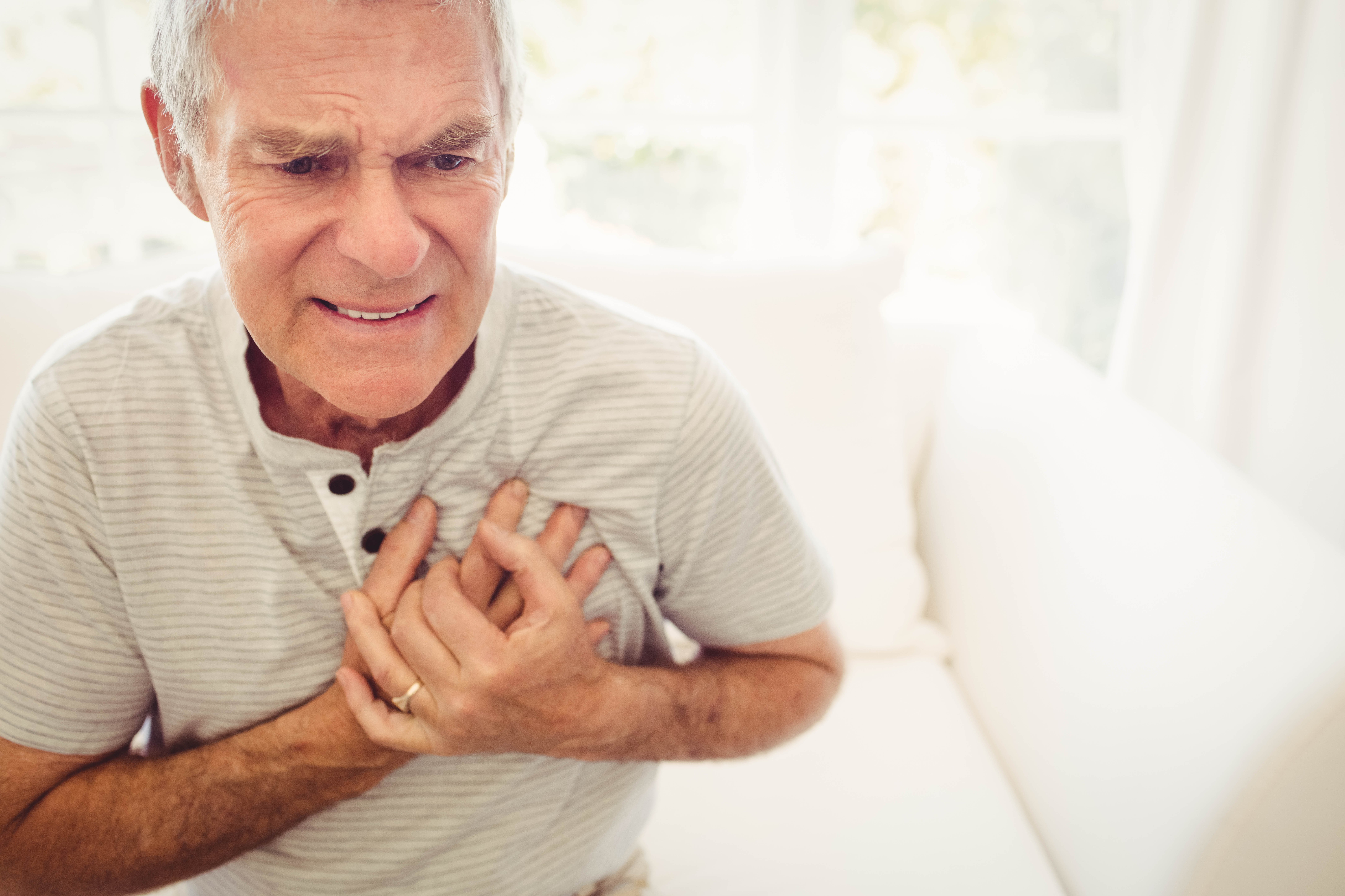 Senior man with pain in the heart in bedroom | Photo: Shutterstock.com
