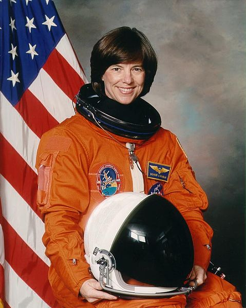 Portrait of Bonnie J. Dunbar in NASA uniform with U.S. flag in the background | Source: Wikimedia Commons