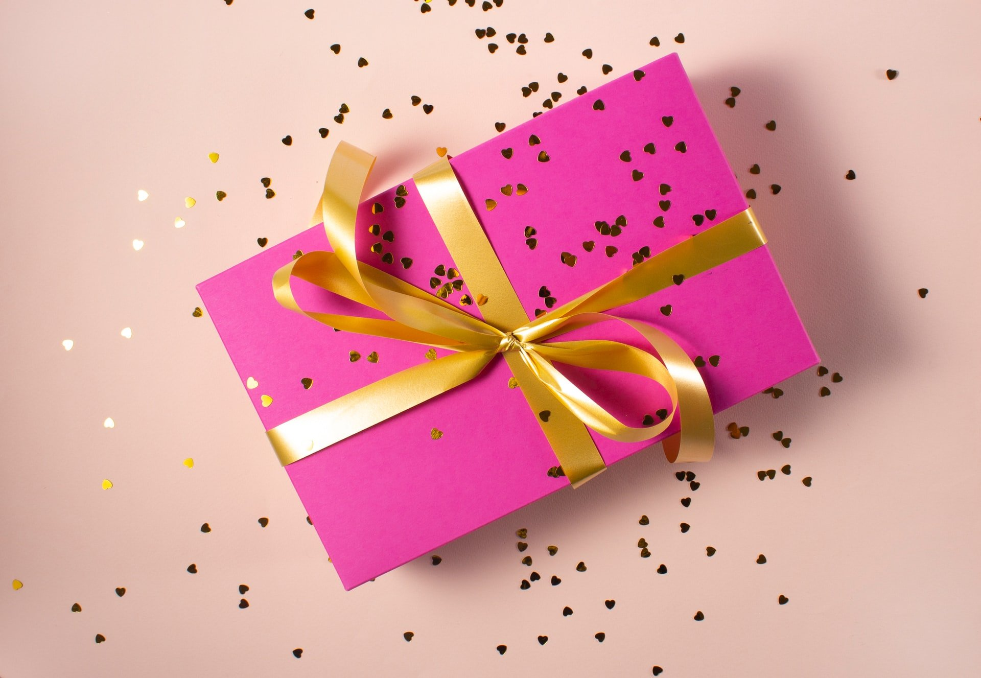 Gift wrapped in pink sheet with golden ribbon   Source: Unsplash