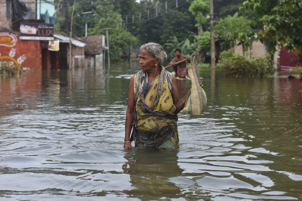 A woman wading through the flooded water in West Bangal. August 6, 2021 | Source: Getty Images