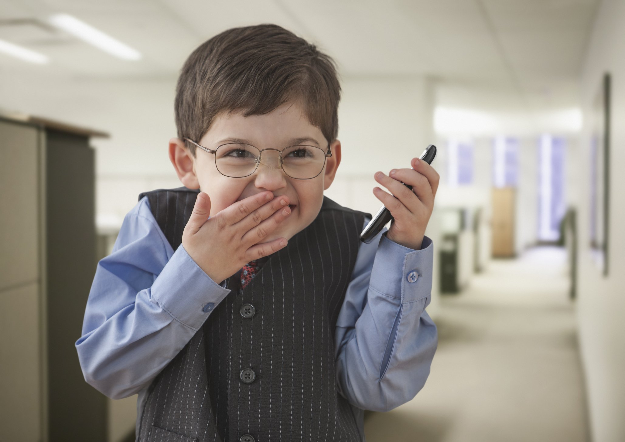 Photo of boy wearing businessman outfit in office | Photo: Getty Images
