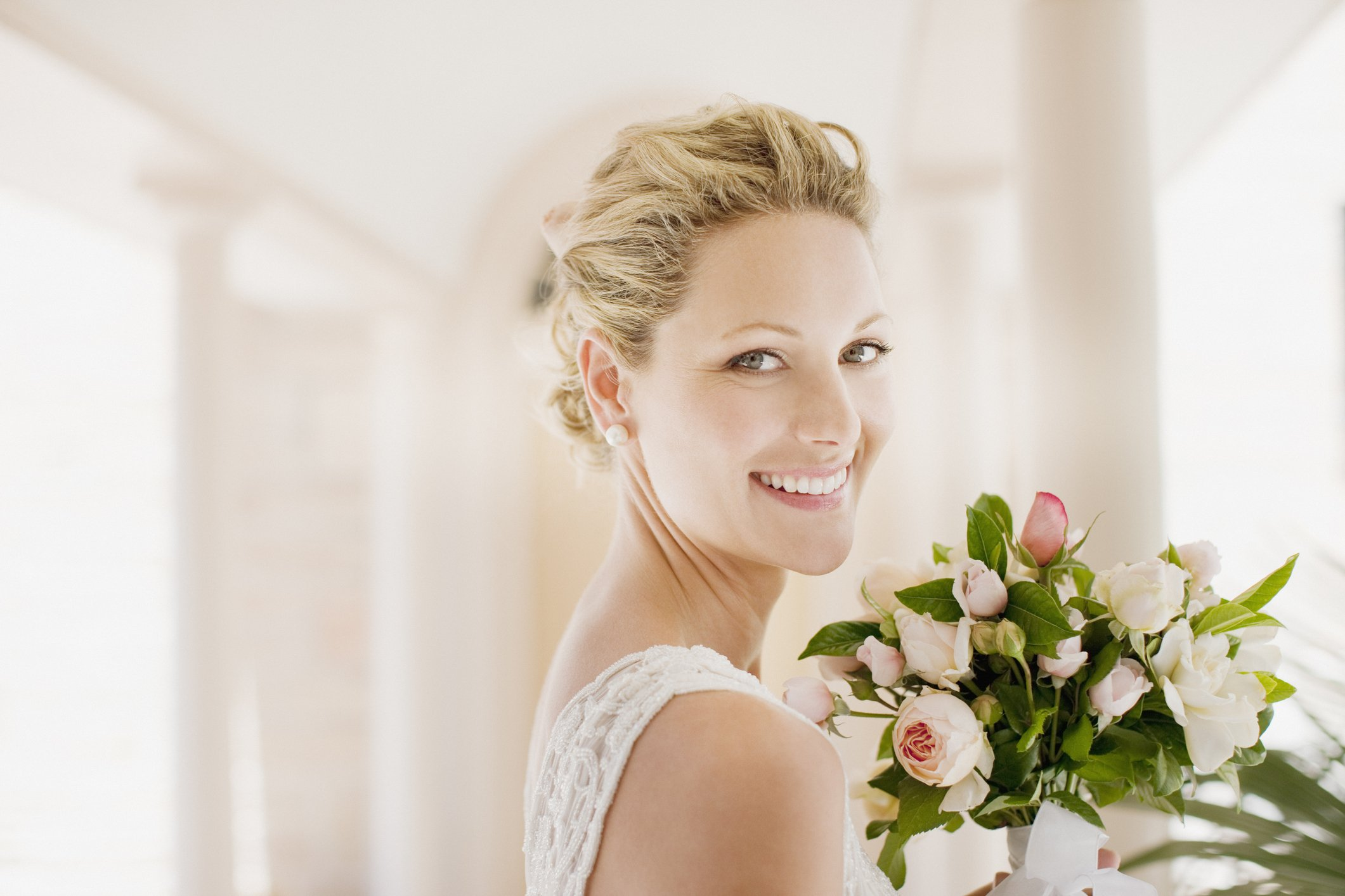 Bride smiling with a bouquet.   Photo: Getty Images