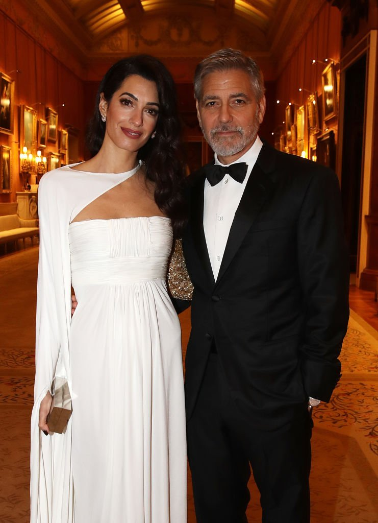 Amal & George Clooney at Buckingham Palace in London, England on March 12, 2019. | Photo: Getty Images