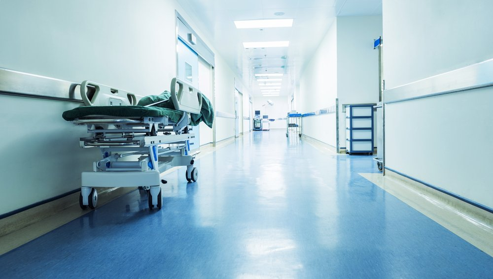 Ahospital hallway withan empty gurney standing on the side | Shutterstock/hxdbzxy