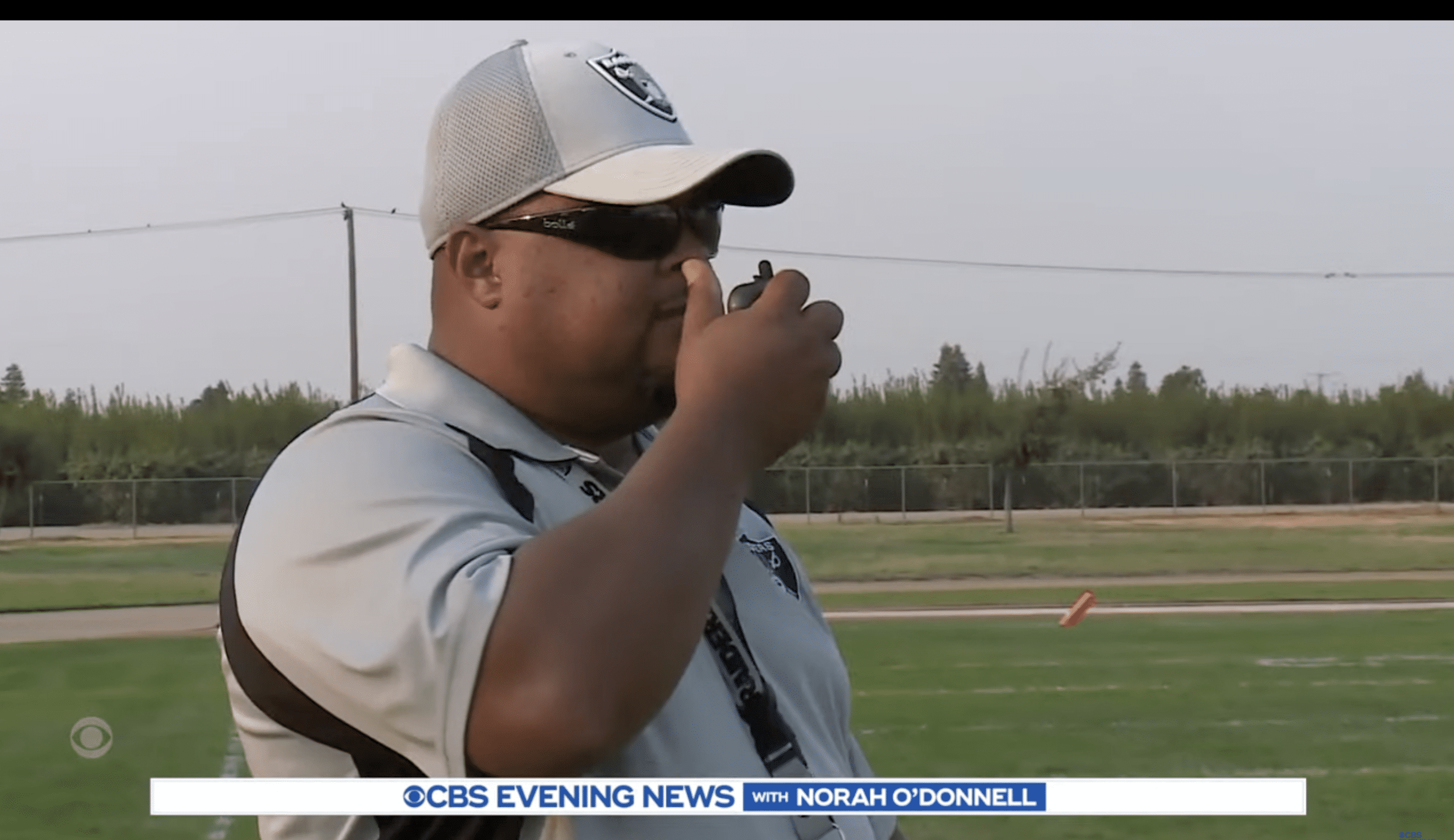 Bracy's dad guides him on the field through a walkie-talkie. | Photo: youtube.com/CBSEveningNews