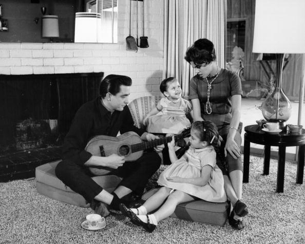 Country singer/songwriter Johnny Cash holds a guitar as his wife Vivian Liberto and daughters, Rosanne Cash and Kathy Cash look on in 1957 | Photo: Getty Images