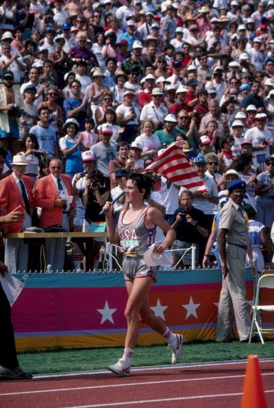 Joan Benoit of the USA carries an American flag as she takes a victory lap around the Los Angeles Memorial Coliseum following her gold medal performance in the first ever women's Olympic marathon race at the 1984 Summer Olympic Games | Source: Getty Images