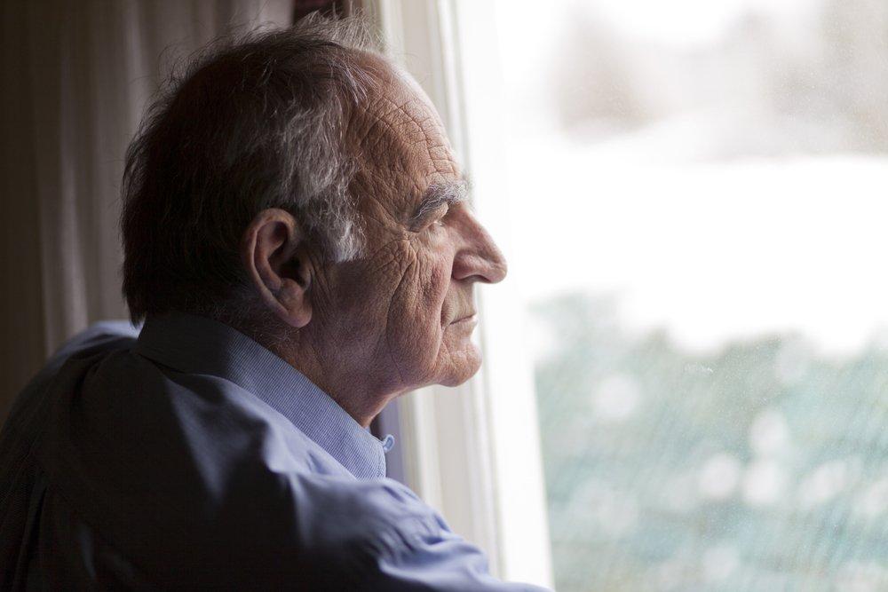 Un homme âgé pensif devant la fenêtre. | Photo : Shutterstock