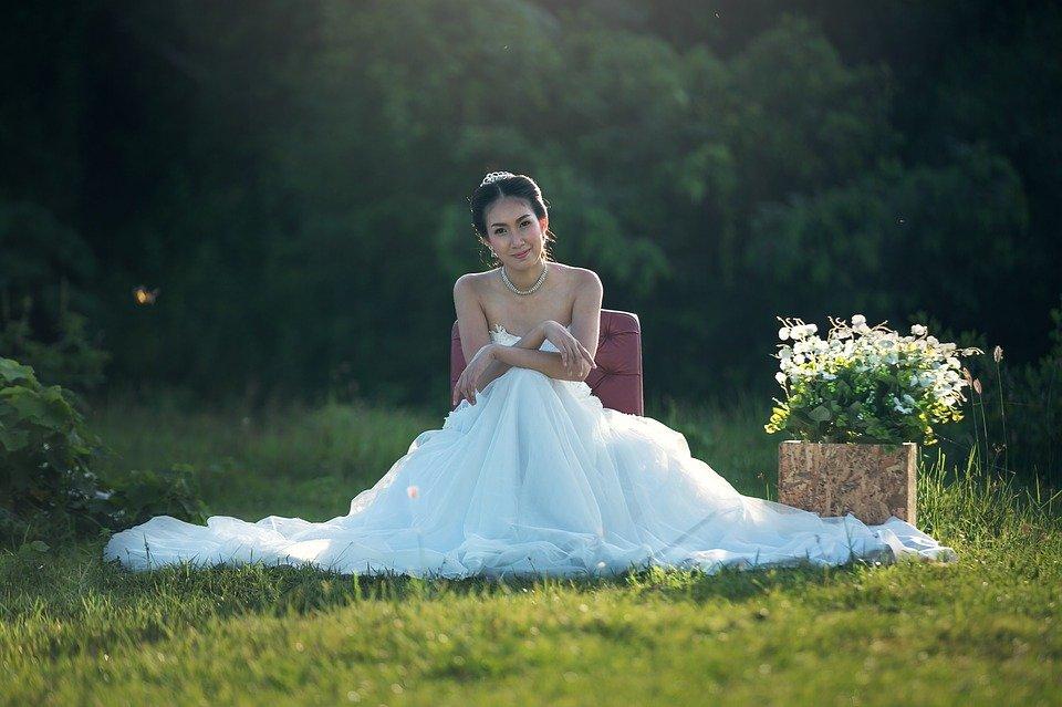Une femme qui s'assit dans une jardin vêtue d'une robe de mariage | Photo : Pixabay