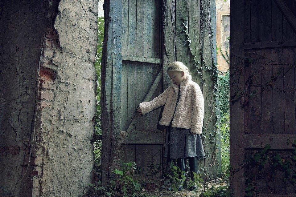 Niña cerca de una puerta de madera. | Imagen: Pixabay