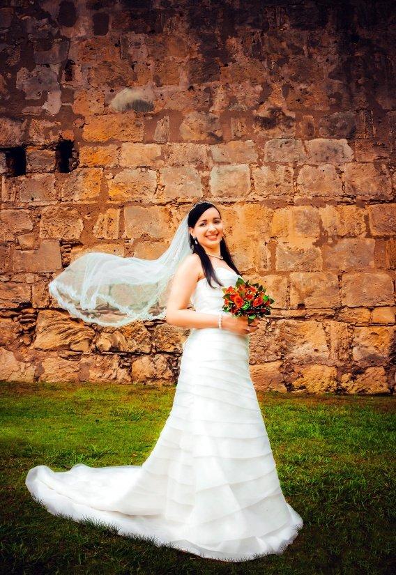 Mujer parada sobre el pasto con vestido de novia y velo, sosteniendo un ramo de flores. | Imagen: Pixnio