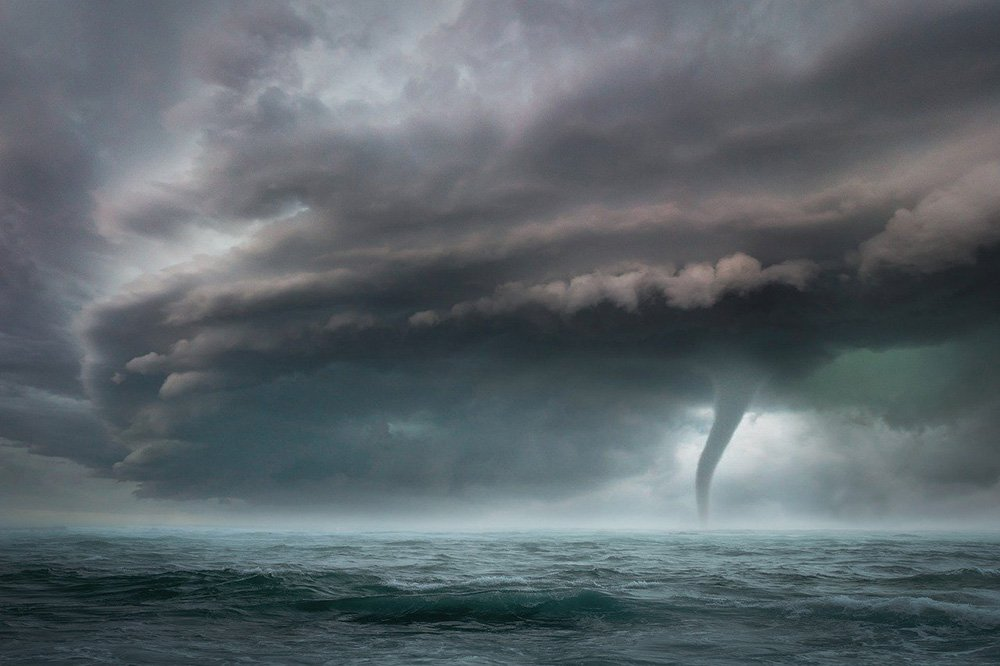 A huge storm takes form in the horizon, with a tornado roaming in open waters. I Image: Pixabay.