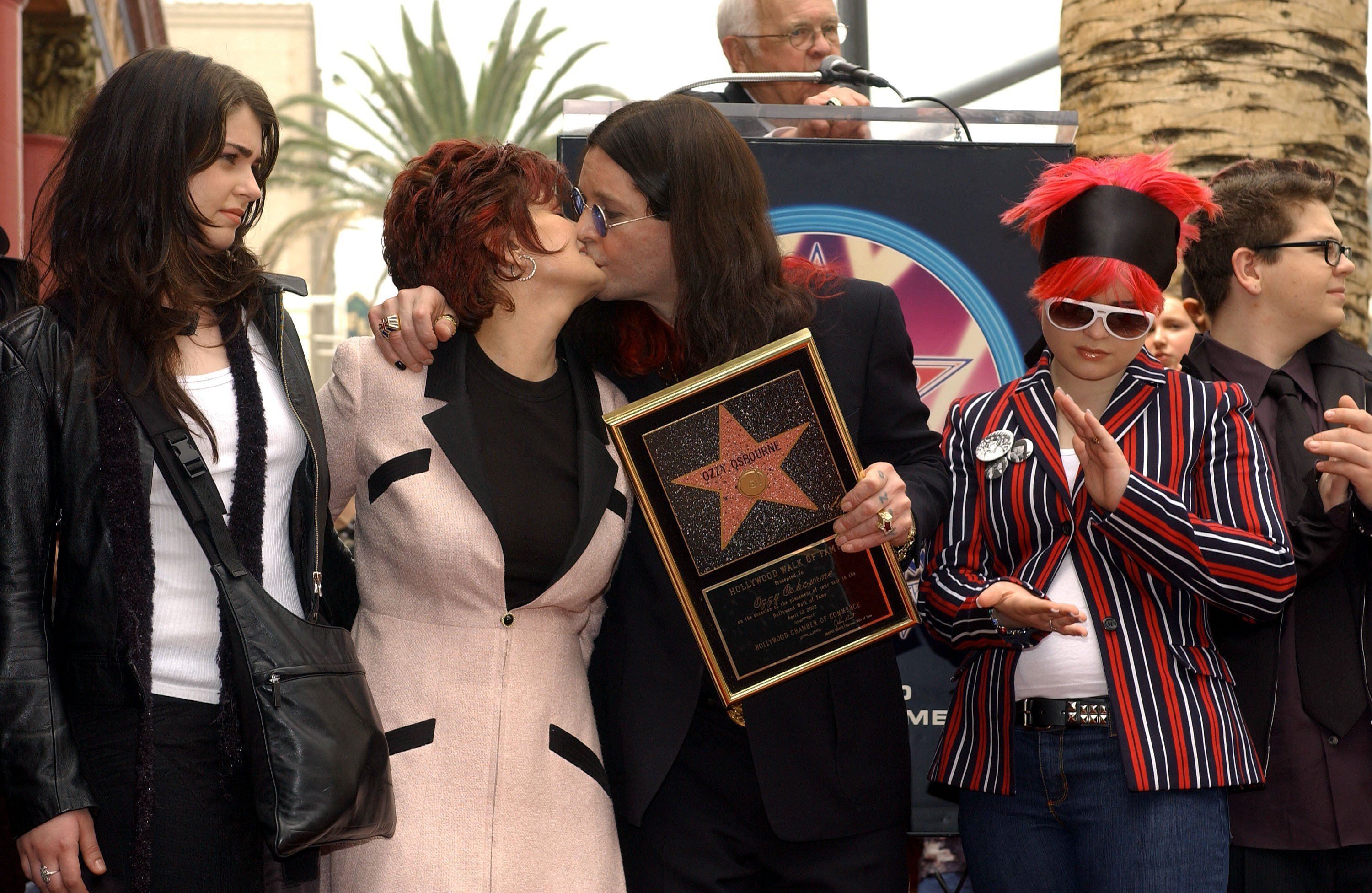 Ozzy Osbourne (C) kisses wife Sharon as daughters Aimee (L) and Kelly look on during the ceremony honoring him with a star on the Hollywood Walk of Fame | Source: Getty Images