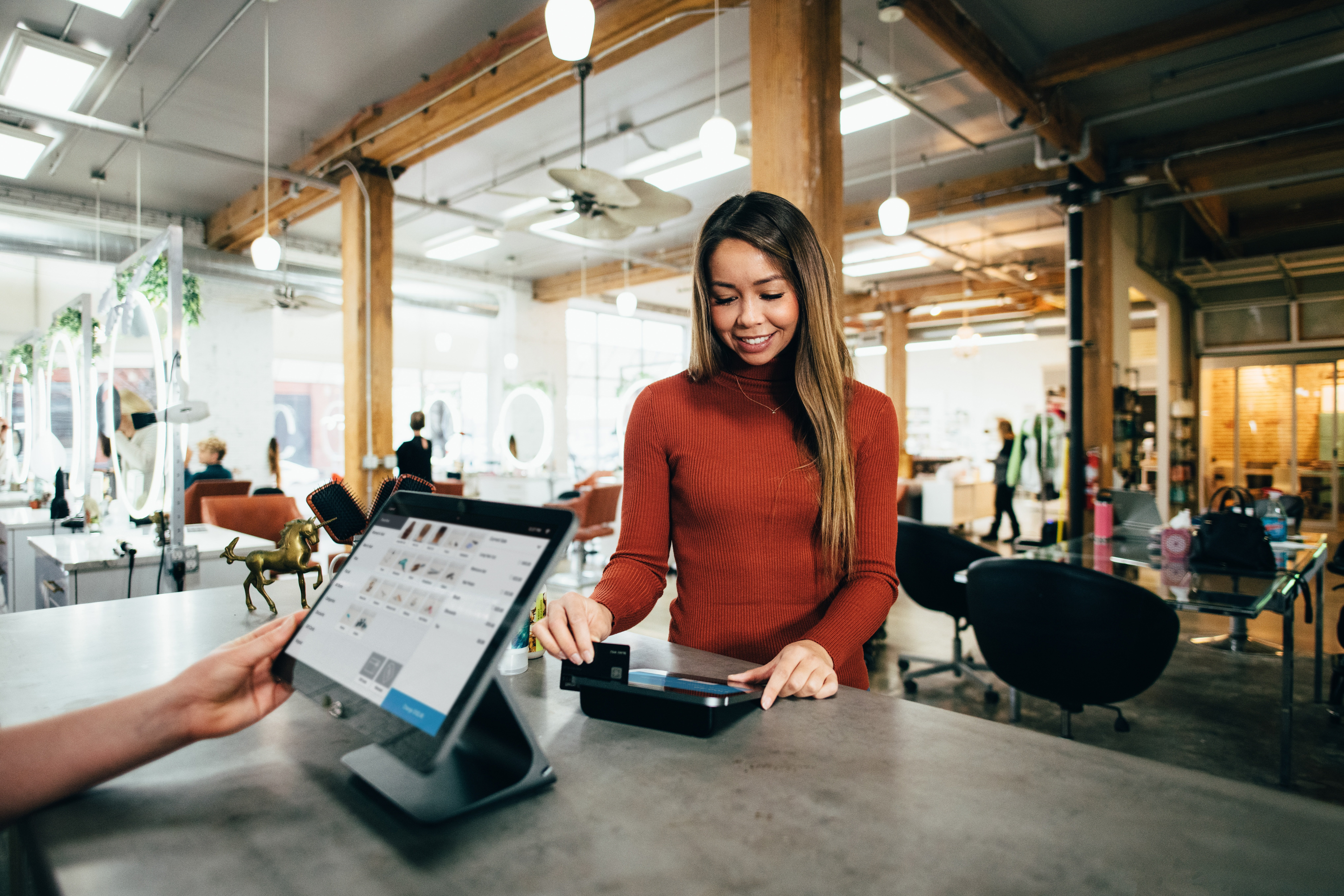 A lady at a counter swiping her card   Source: Unsplash.com