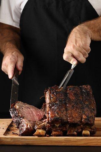 Un chef découpant l'extrémité d'un rôti de bœuf fraîchement cuit   Photo: Getty Images