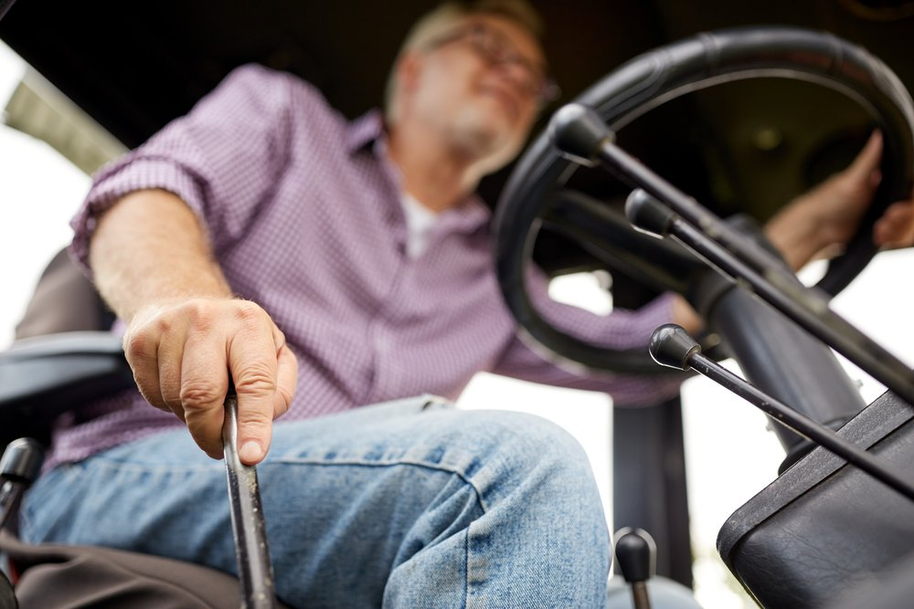 A senior man driving a tractor on afarm | Photo: Shutterstock/Syda Productions
