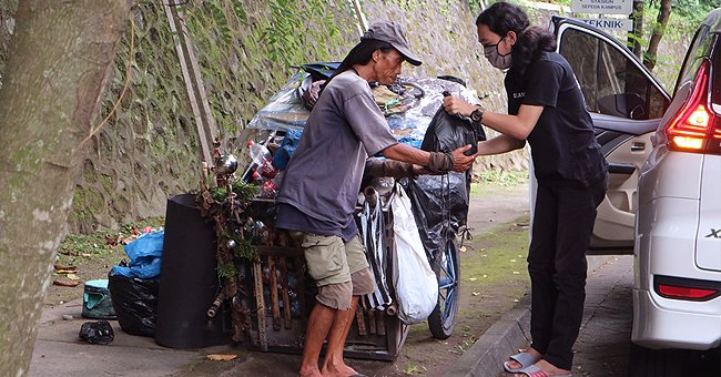 A woman giving a homeless person basic items from the boot of her car   Photo: Shutterstock
