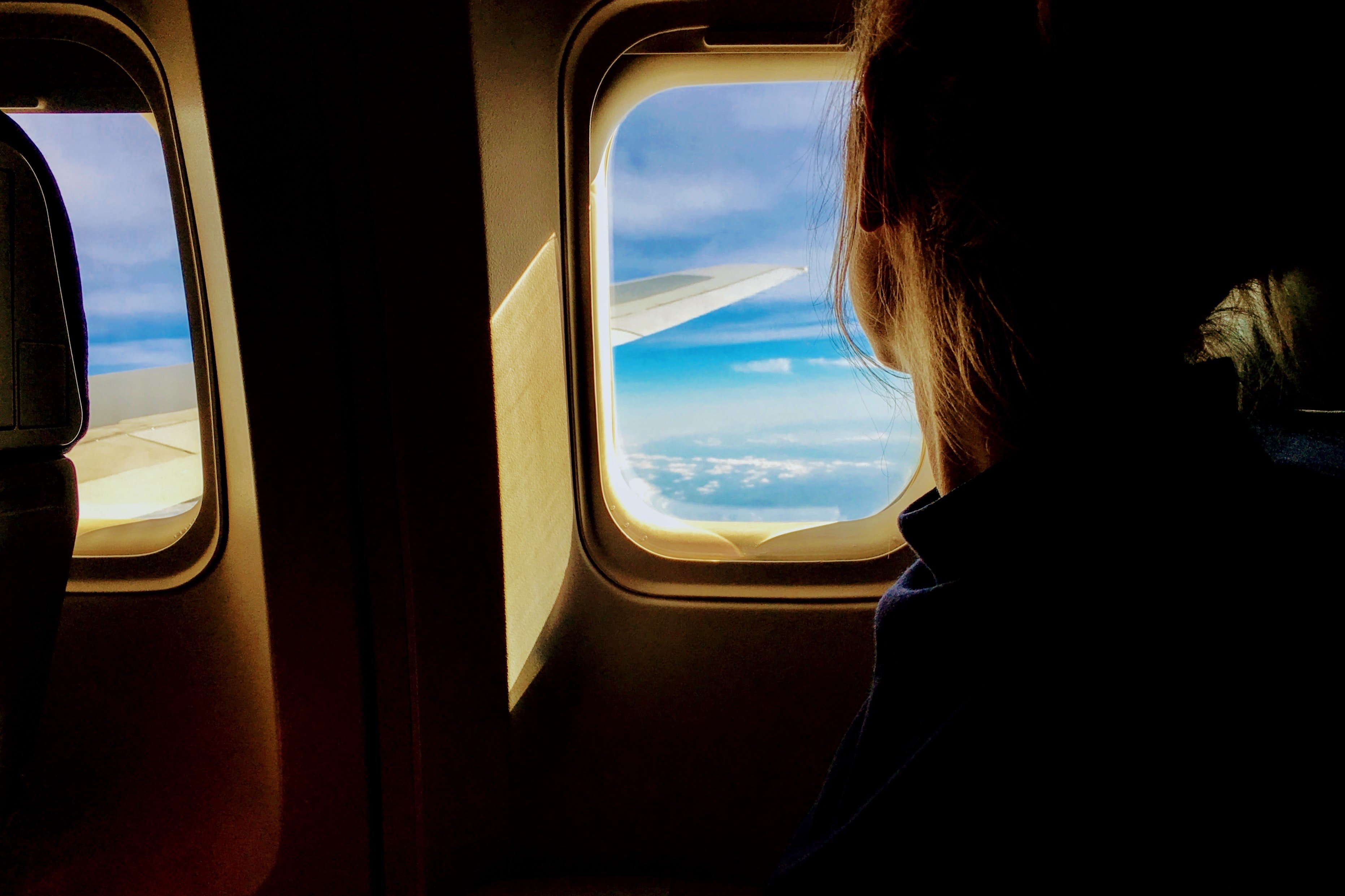 Blonde woman looking out of a plane window. | Source: Pexels/Tim Gouw