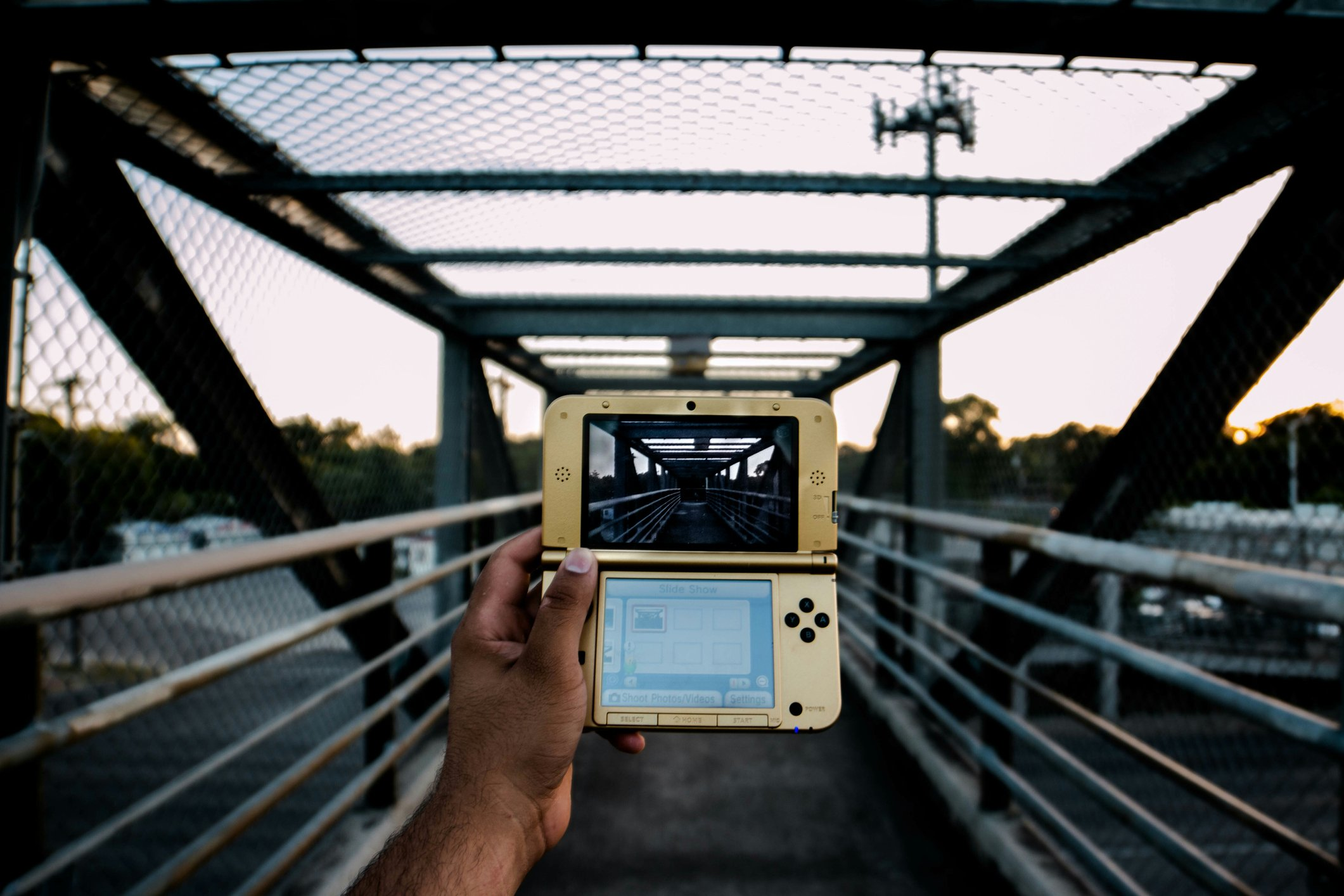 A Man Photographed holding a Nintendo 3Ds on a bridge. | Photo: Getty Images