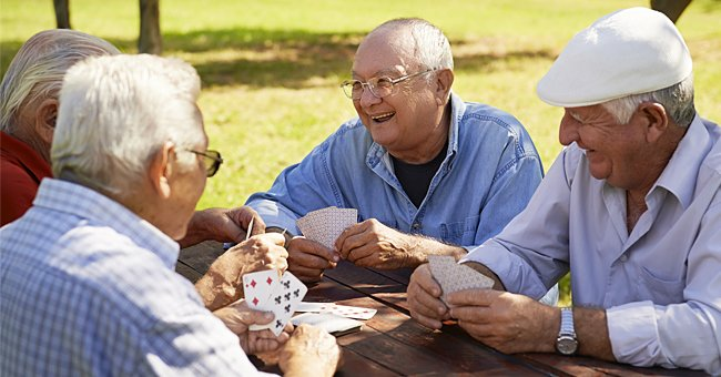 Older adults playing cards outdoors. | Photo: Shutterstock