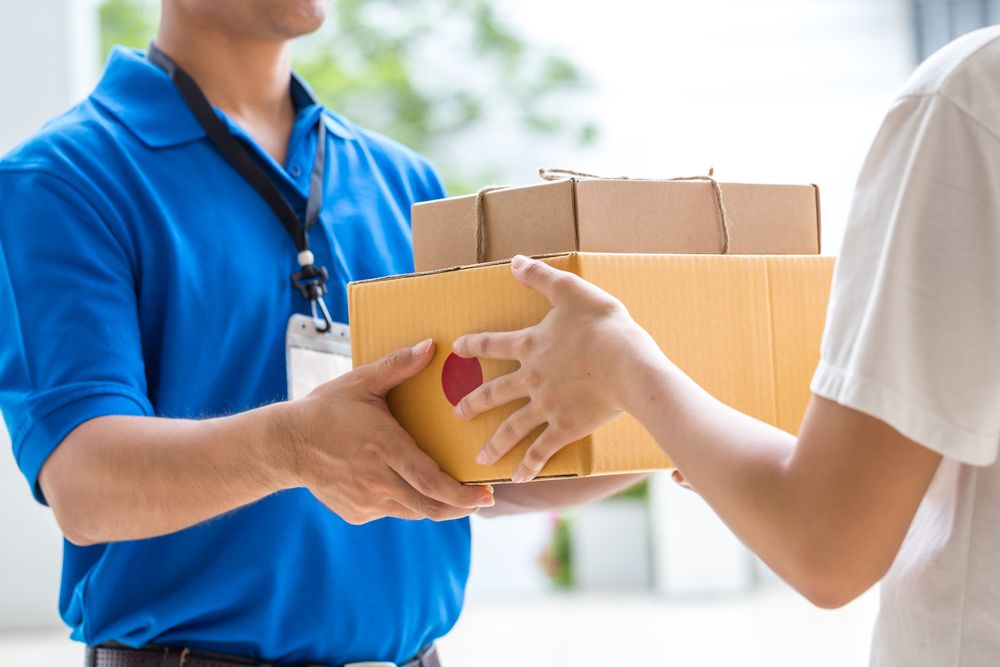 A delivery man hands over a package.   Source: Shutterstock