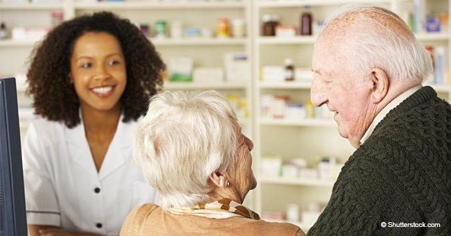 Un couple de personnes âgées passe devant une pharmacie tout en discutant de leur désir de se marier