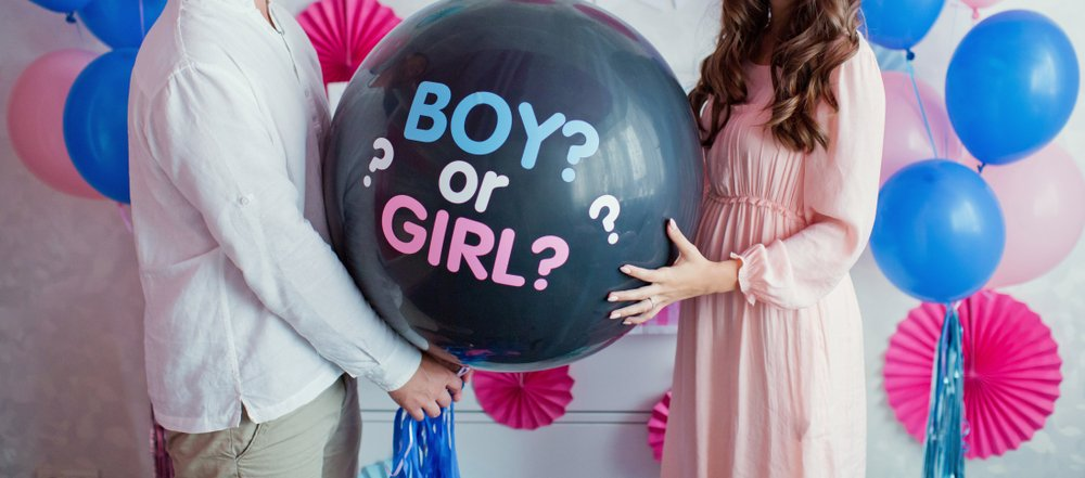 """Expecting parents holding a black balloon with """"boy or girl?"""" in gender reveal party.   Photo: Shutterstock."""