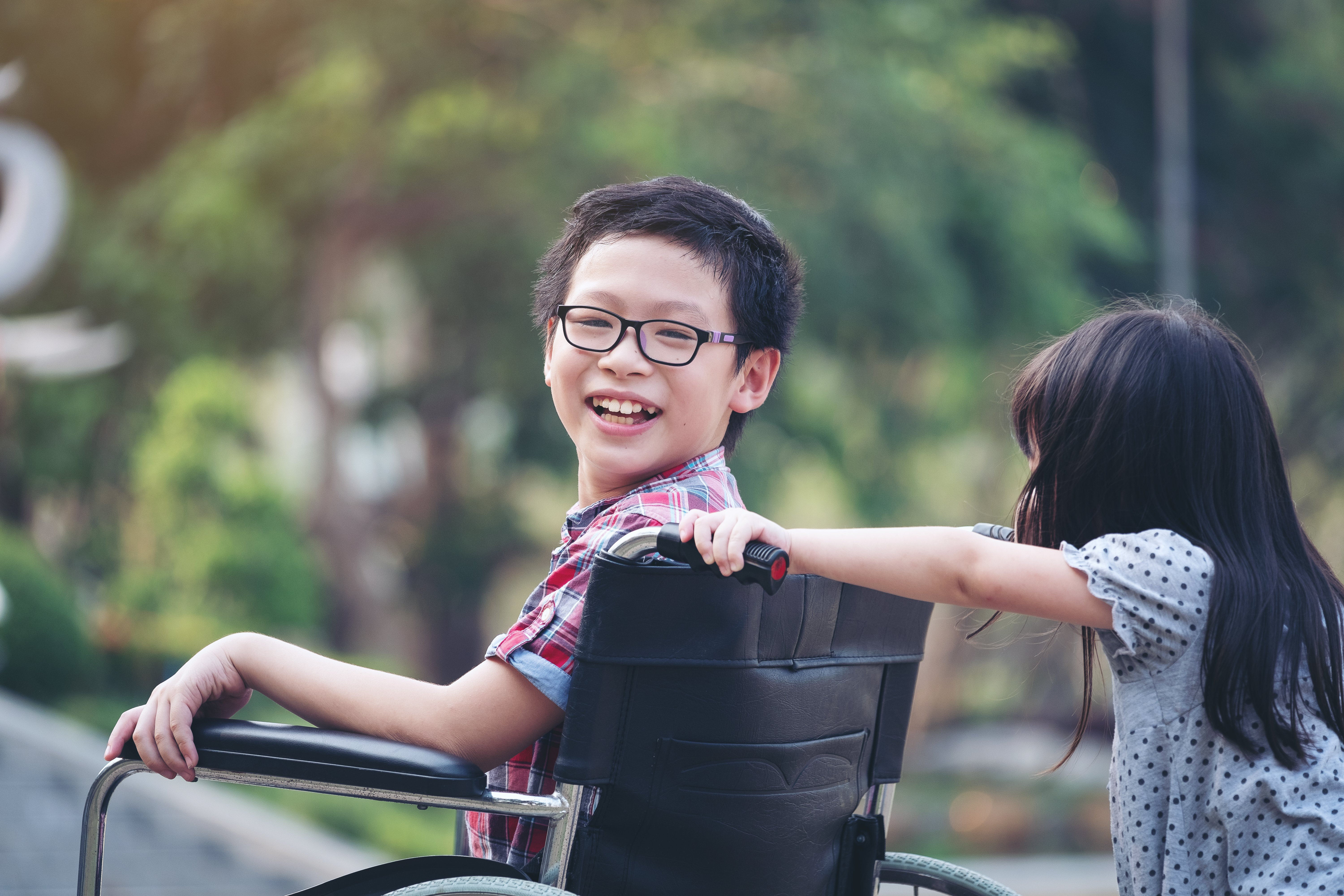 Portrait Of Happy Boy Sitting On Wheelchair With Sister|Photo: Getty Images
