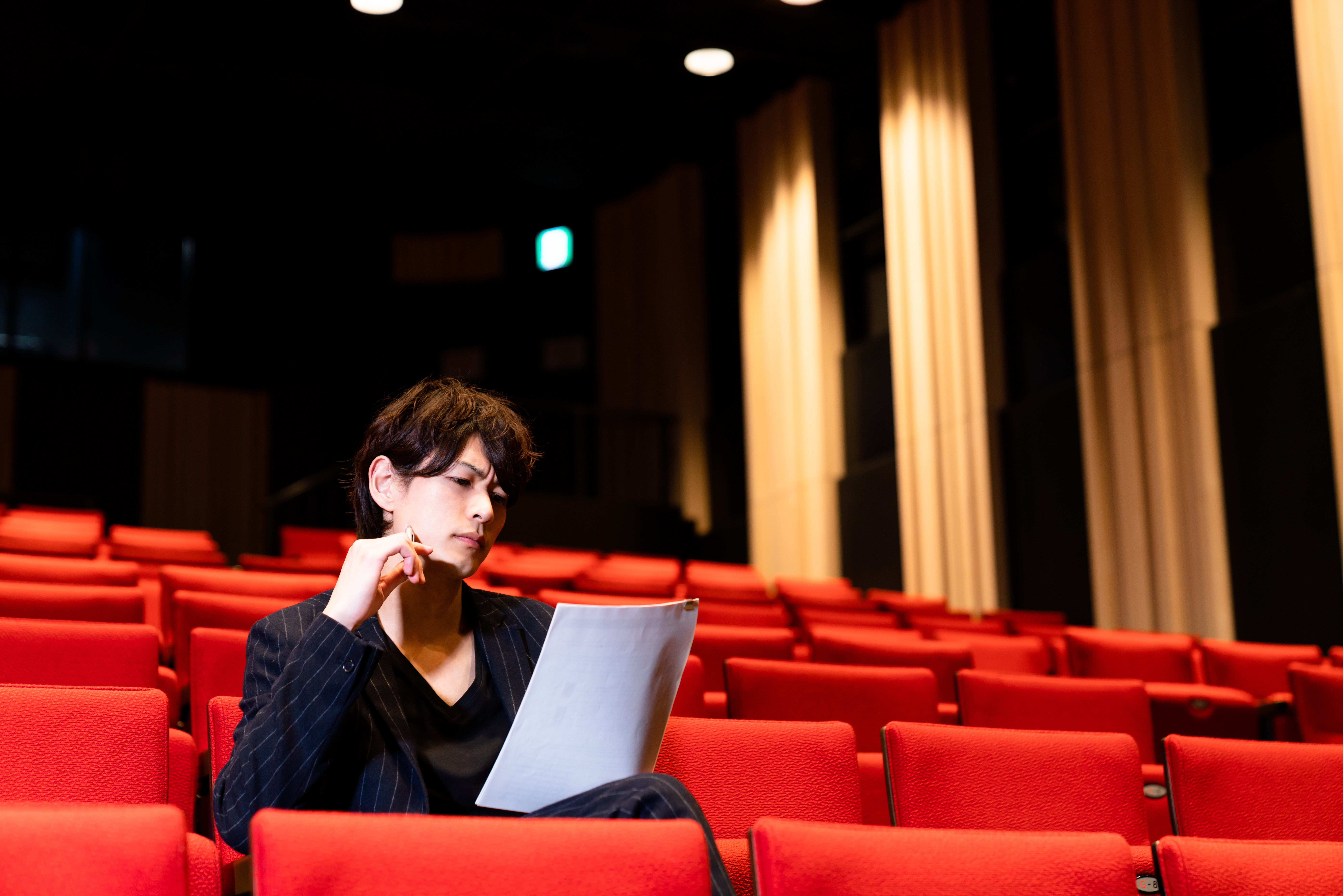 A theatre judge seated on one of the theatre seats.   Source: Shutterstock