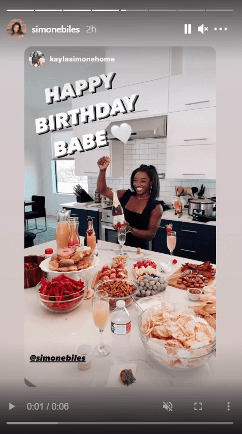 A screenshot from a video of Simone Biles posing in front of a table with several delicacies   Source: Instagram/simonebiles