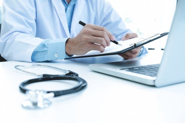 A doctor completing forms. Image credit: Pixabay
