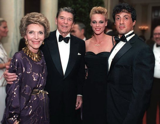 President and Nancy Reagan posing with Sylvester Stallone and Brigitte Nielsen during a state dinner for Prime Minister Lee Kuan Yew of Singapore. | Source: Wikimedia Commons