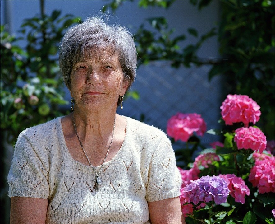 A portrait of an old woman beside the flowers.   Photo: pixabay.com